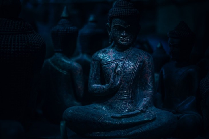 Dark-Blue-Buddhist-Statue-Sitting-in-the-Dark-with-Other-Buddhist-Statues-in-the-Background