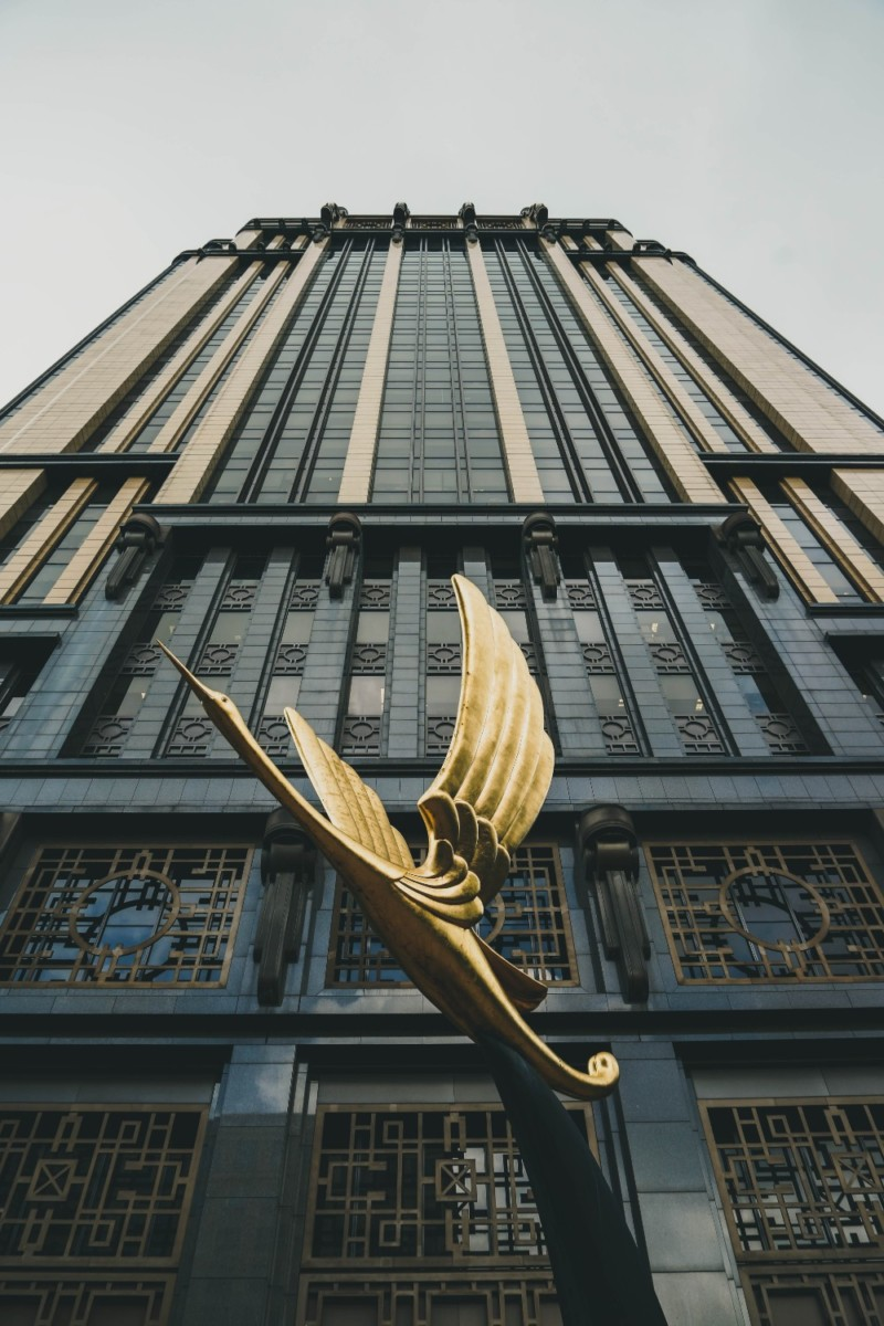 Golden-Bird-Statue-in-front-of-a-Tall-Dark-Building