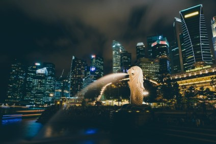 Illuminated-Statue-with-the-Body-of-a-Fish-and-the-Head-of-a-Lion-Spitting-Water-in-a-Fountain