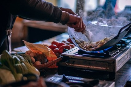 Close-up-Shot-of-a-Man-Frying-Food-on-a-Gas-Stove