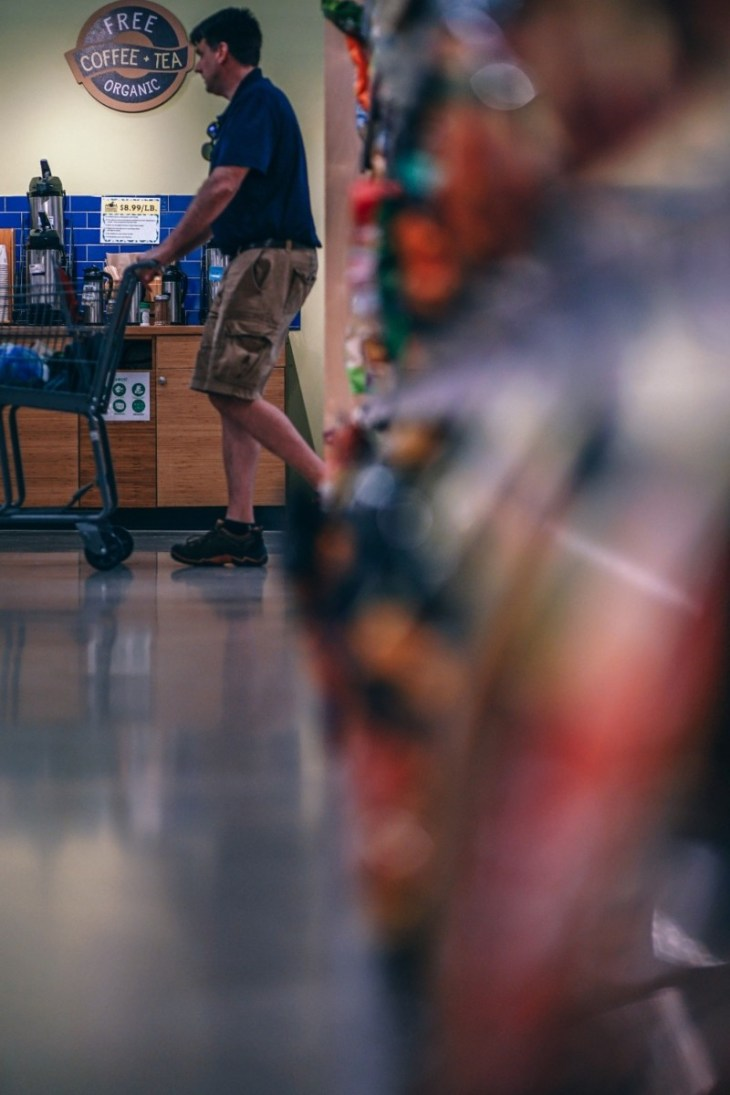 Man-Pushing-a-Grocery-Cart-Photographed-Behind-a-Full-Shelf