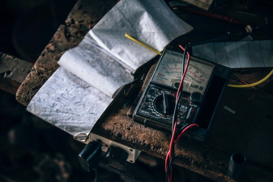 Notebook-with-Sketches-on-a-Table-next-to-an-old-Voltmeter