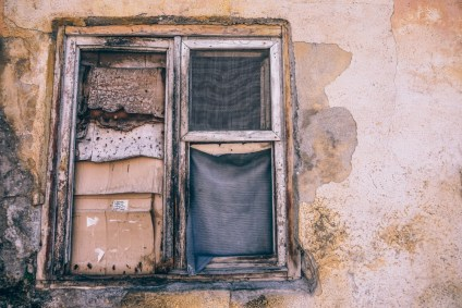 Old-and-Damaged-Window-with-Cardboards-instead-of-Glass