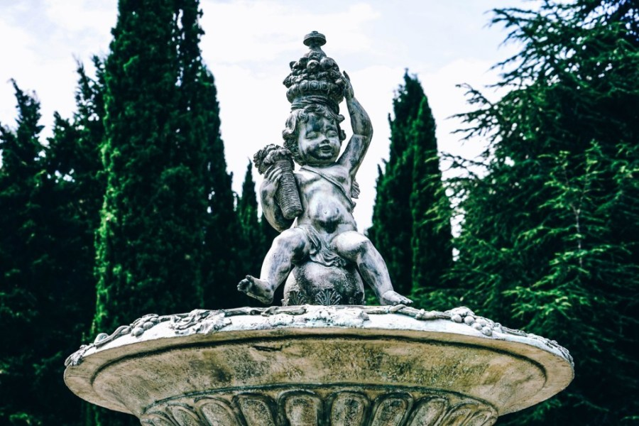 White-Statue-Fountain-Photographed-in-front-of-Tall-Trees