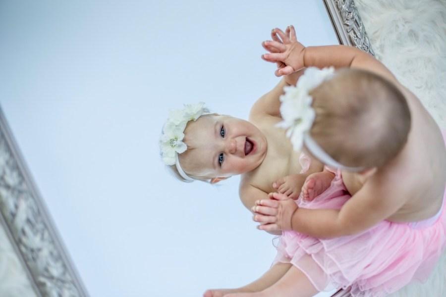toddler-facing-mirror-while-smiling
