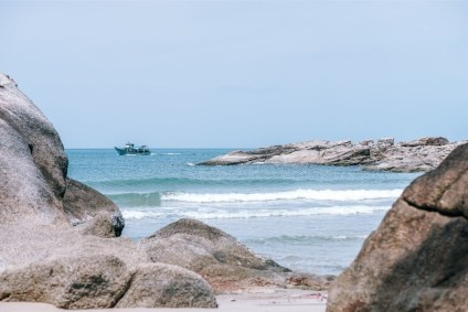 Fishing-Boat-Photographed-from-the-Beach-Behind-Rocks