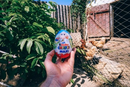 Holding-a-Kinder-Surprise-Egg-in-front-of-a-Chicken-Coop