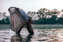 Nepali-Woman-Holding-a-Round-Fishing-Net-to-Catch-Small-Fish-at-Sunset