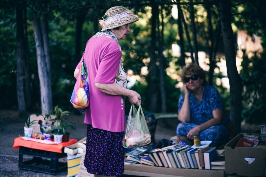 Old-Lady-Looking-at-an-Outdoor-Book-Stand
