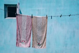 Towels-Drying-on-a-Cloth-Drying-Wire-with-a-Big-Light-Blue-Wall-in-the-Background