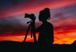 silhouette-of-woman-holding-camera-at-night