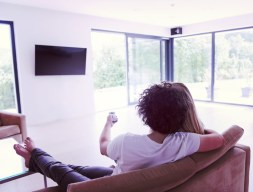 rear-view-of-couple-watching-television-PYEVWAK