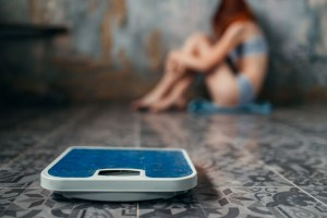 anorexic woman sitting on the floor weight loss pmxbke