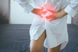 woman having painful stomachache at home RYVCYJ
