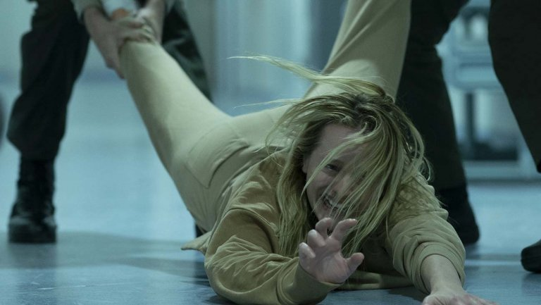 Elisabeth Olsen being dragged at a mental asylum in The Invisible Man