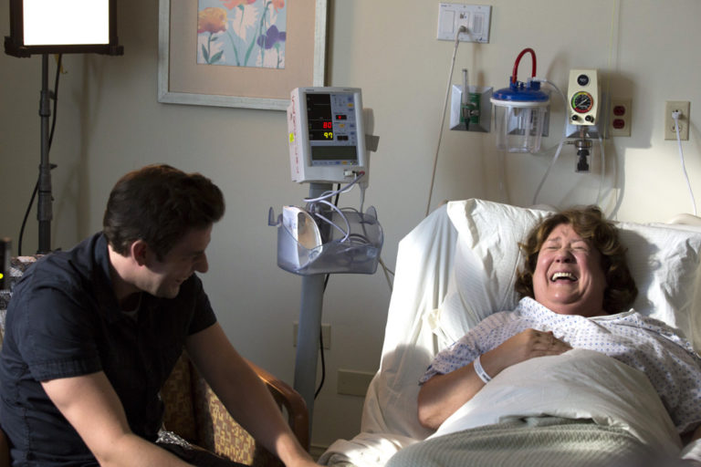 John Krasinski laughing with Margo Martindale in The Hollars