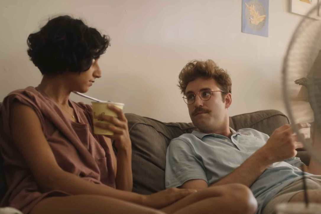 John Paul Reynolds and Sunita Mani sitting on a couch in Save Yourselves
