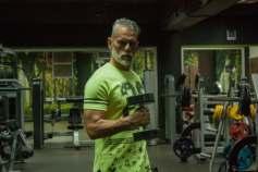 gespierde grijze man op leeftijd in groen shirt met halter
