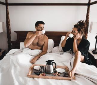 man en vrouw die in bed koffie drinken na de sex