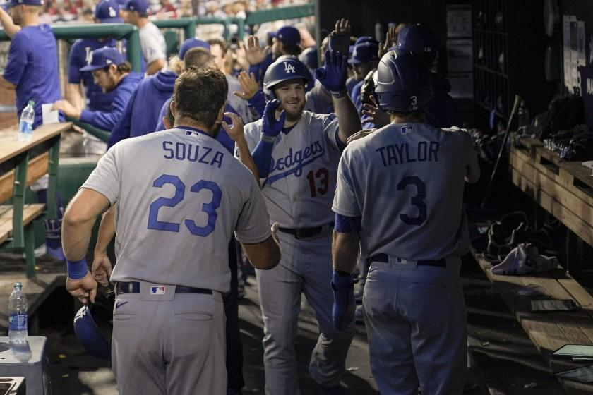 Los Angeles Dodgers' Max Muncy, center, is greeted in the dugout by teammates after hitting a grand slam off Washington Nationals starting pitcher Patrick Corbin during the fifth inning of a baseball game, Thursday, July 1, 2021, in Washington. Dodgers' Steven Souza Jr. (23), Chris Taylor (3) and Justin Turner, not visible, scored on the home run. (AP Photo/Julio Cortez)