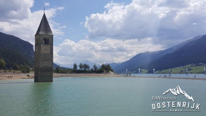 Reschensee met de kerktoren van Graun. Op de achtergrond de gletsjer van de Ortlergruppe