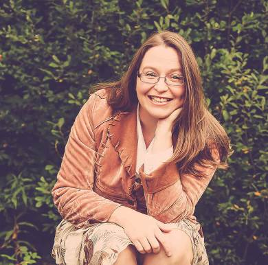 Author Dawn Chapman seated leaning forward