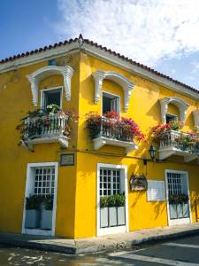 Colorful yellow home with flower window boxes, Cartagena, Colombia, Fantasy Aisle travel