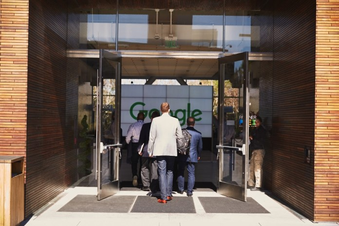 Several people entering a Google office building
