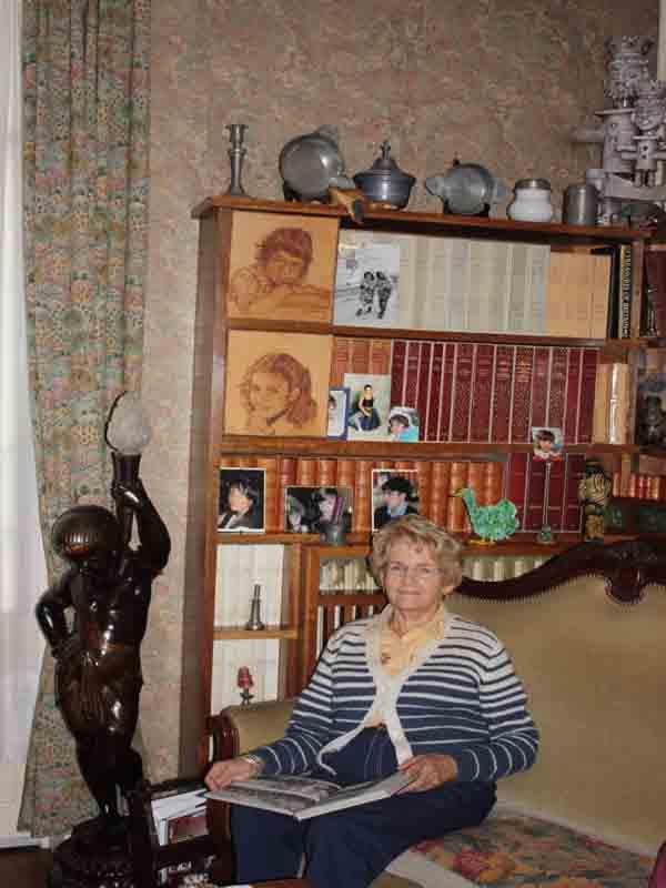 Geneviève dans son salon au dessous de deux portraits qu'elle avait fait de ses enfants