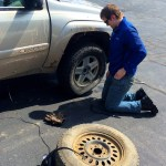 Ethyn helps change the flat tire.