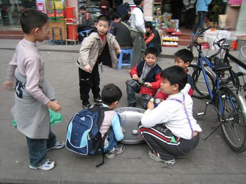 Kids playing with their tops in the streets and back alleys near the Chen Family Temple in Guangzhou, China