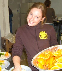 Girl holding pan of orange slices puting them on plates of food