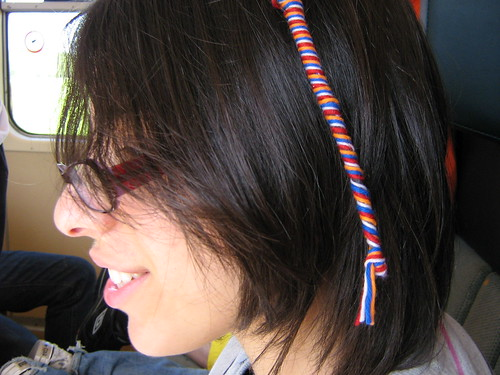 Kat with orange, red, white, and blue wool braided into her hair