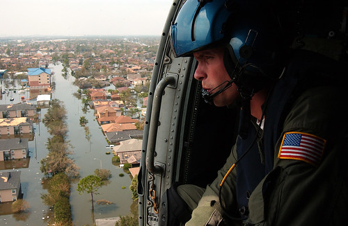 Keeping Watch: A Coastie keeps a sharp lookout from a helicopter over flooded New Orleans