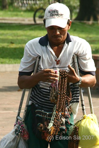 Disabled street vendor on crutches waiting for customer in front Manila Cathedral, religious items, wooden rosaries,  Buhay Pinoy Philippines Filipino Pilipino  people pictures photos life Philippinen Binondo
