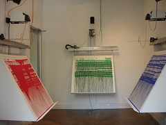 Photo of Remembrancer installation showing the three panels and robotic painters.
