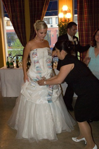 pinning money on the wedding dress