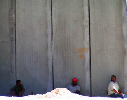 three people by the wall near the Qalandiya Ch...
