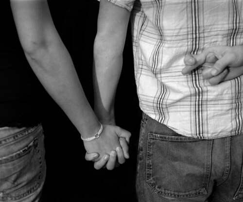 two people holding hands, one person crosssing fingers behind their back