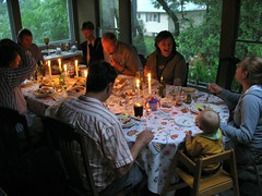 A family gathers around the table for a meal