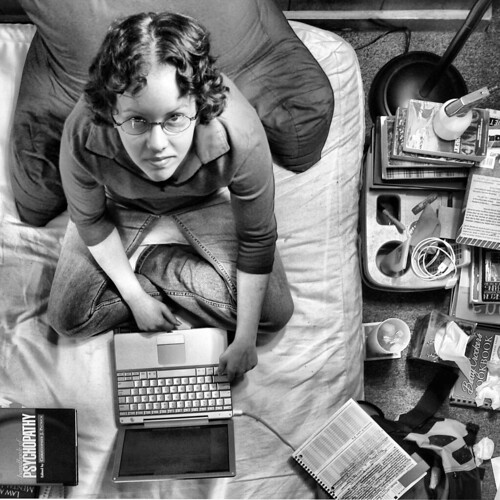 young woman doing homework on her bed