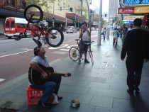 Man balances bicycle on head whilst playing guitar