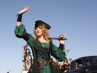 Irish woman with long wavy red hair, in green pirate costume, waving.