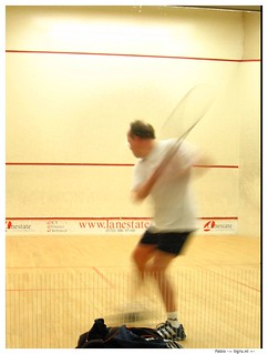 Man playing squash - the image is blurred because he is moving fast.