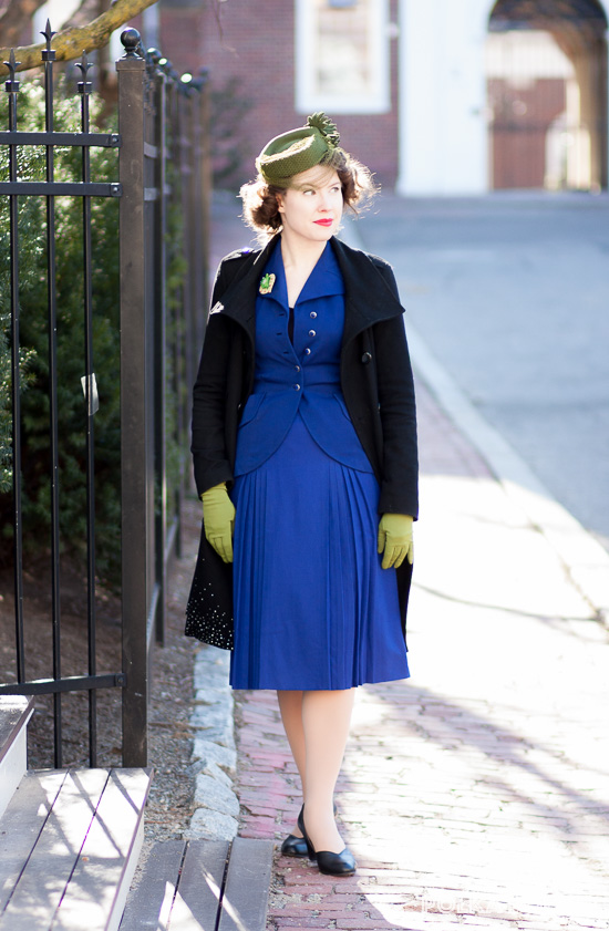 A springy late winter outfit with nods to 1940s style, featuring a royal blue suit paired with spring green accessories and a sparkly black overcoat