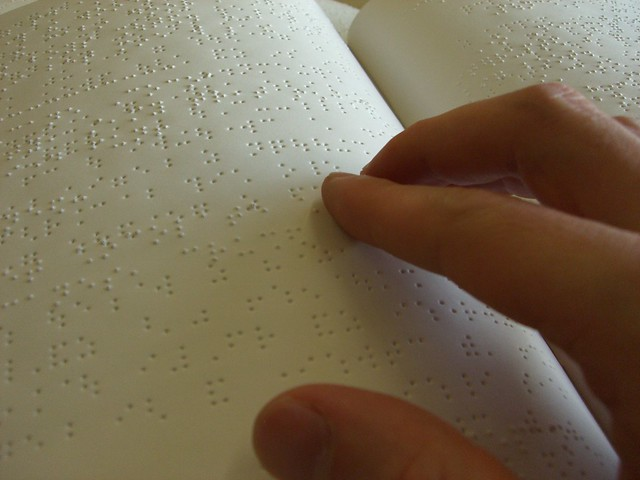Imagen de una mano que toca una hoja en braille