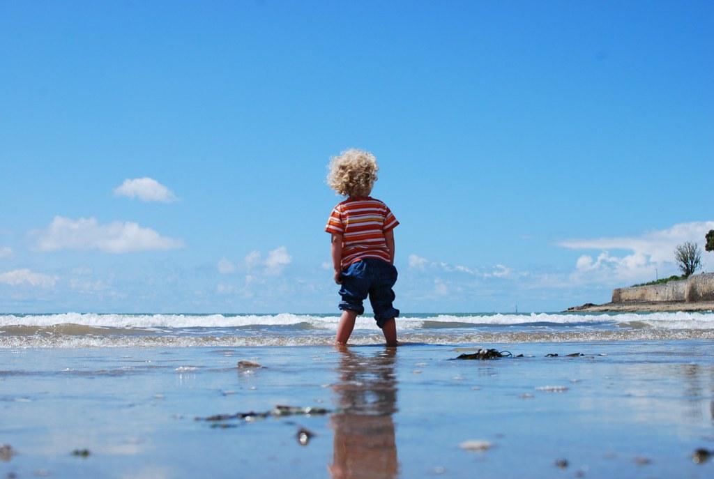 Imagen gratis de un niño en la orilla del mar