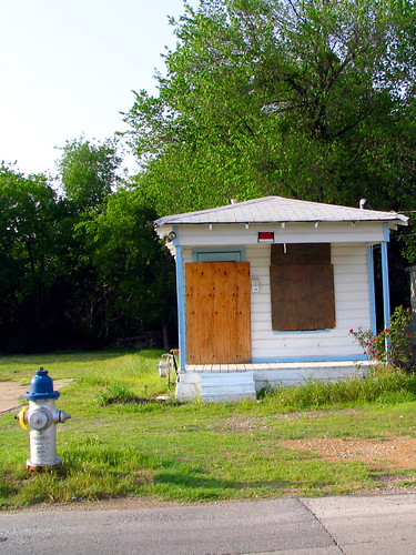 small boarded up house, with a tiny for rent sign above the porch, grass and trees in background, blue and white fire hydrant in foreground