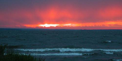 sun setting inside a band of thunderstorm clouds on Georgian Bay by gnawledge wurker