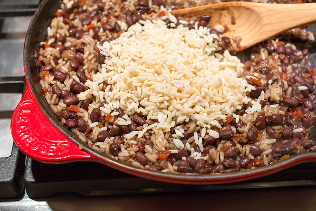 adding the rice to gallo pinto pan